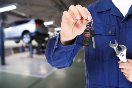Auto mechanic holding key with tools and workshop on background. Car service concept