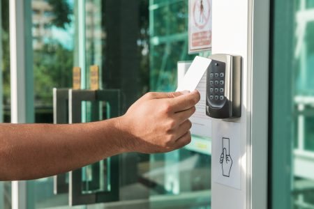 Hand using security key card scanning to open the door to entering private building. Home and building security system